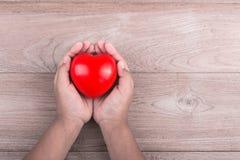 Concept d'amour : La femme remet tenir le coeur rouge sur l'étiquette en bois brune Photographie stock libre de droits