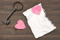 Concept d'amour non récompensé La clé de vintage, deux a chiffonné le coeur, blanc Photographie stock libre de droits
