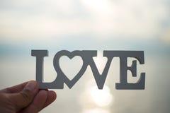 Concept d'amour tenir un coeur dans des mains à la mer Photographie stock