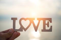 Concept d'amour tenir un coeur dans des mains à la mer Images libres de droits