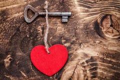 Concept d'amour Vieille clé et un coeur sur le fond en bois Photos stock