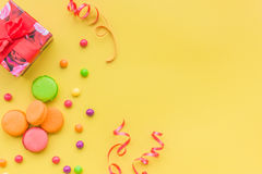 Concept d'anniversaire avec le cadeau et les bonbons enveloppés sur le copyspace jaune de vue supérieure de fond Images stock