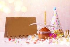 Concept d'anniversaire avec le petit gâteau à côté de la carte de voeux vide Photographie stock libre de droits