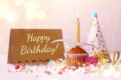 Concept d'anniversaire avec le petit gâteau et la bougie à côté de la carte de voeux Images stock