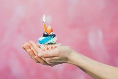Concept d'anniversaire, peu de gâteau avec une bougie dans des mains Photos stock
