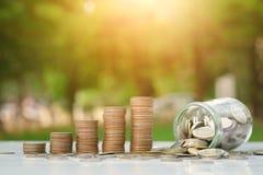 Concept d'argent d'économie avec l'élevage de pile de pièce de monnaie et affaires de bouteille sur le fond de coucher du soleil Image stock