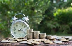 Concept d'argent d'économie avec l'élevage de pile de pièce de monnaie d'argent et les clo d'alarme Images stock