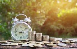 Concept d'argent d'économie avec l'élevage de pile de pièce de monnaie d'argent et les clo d'alarme Image libre de droits