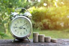 Concept d'argent d'économie avec l'élevage de pile de pièce de monnaie d'argent et les clo d'alarme Photo stock
