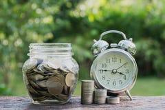 Concept d'argent d'économie avec l'élevage de pile de pièce de monnaie d'argent et les clo d'alarme Photos stock