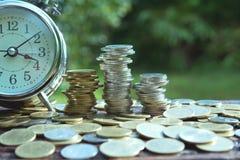 Concept d'argent d'économie avec l'élevage de pile de pièce de monnaie d'argent et les clo d'alarme Images libres de droits