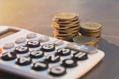 Concept d'argent d'économie avec l'élevage et le calculato de pile de pièce de monnaie d'argent Photos stock
