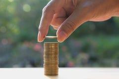 Concept d'argent d'économie avec la main tenant la pile de pièce de monnaie et de pièce de monnaie d'argent Photographie stock libre de droits