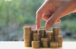 Concept d'argent d'économie avec la main tenant la pile de pièce de monnaie et de pièce de monnaie d'argent Image libre de droits