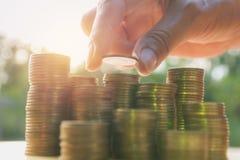 Concept d'argent d'économie avec la main tenant la pile de pièce de monnaie et de pièce de monnaie d'argent Photo libre de droits