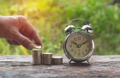 Concept d'argent d'économie et main de l'homme mettant la pile de pièce de monnaie d'argent Photo stock