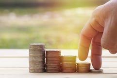 Concept d'argent d'économie, main masculine mettant l'élevage de pile de pièce de monnaie d'argent Photos stock