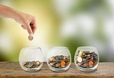Concept d'argent d'économie Remettez tenir mettre des pièces de monnaie dans en trois étapes Image libre de droits