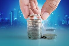 Concept d'argent d'économie main mettant la pièce de monnaie aux piles de pièces de monnaie Image stock