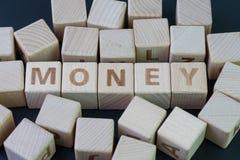 Concept d'argent, de finances ou d'épargne par le bloc en bois de cube avec l'alphabet construisant l'argent de mot au centre su images stock