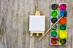 Concept d'art de peinture Chevalet miniature blanc et peintures colorées multi avec la brosse sur le bureau en bois images libres de droits