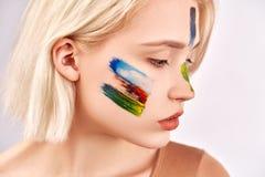 Concept d'art de visage La femme agréable avec le beau maquillage d'art, a les cheveux blonds courts, poses sur le fond blanc photo stock