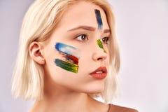 Concept d'art de visage La femme agr?able avec le beau maquillage d'art, a les cheveux blonds courts, poses sur le fond blanc photographie stock libre de droits