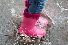 Concept d'automne La fille dans les bottes roses sautant dans les magmas après pluie dehors photos stock