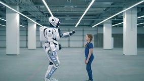 Concept d'avenir Robot blanc et fille touchant des mains, vue de côté banque de vidéos