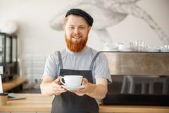 Concept d'entrepreneur de café - portrait de jeune barman caucasien barbu heureux dans le tablier avec le lookin sûr photos libres de droits