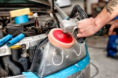 Concept d'entretien automobile avec un mécanicien nettoyant les phares de la voiture Images stock