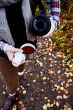 concept d'envie de voyager et de voyage Femme versant une boisson chaude dans la tasse du thermos Thé potable dehors images stock