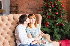 Concept d'hiver, d'amour, de couples, de Noël et de personnes - homme et femme de sourire étreignant au-dessus du fond d'arbre de Images libres de droits