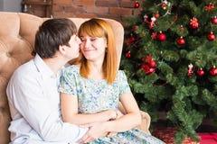 Concept d'hiver, d'amour, de couples, de Noël et de personnes - homme et femme de sourire étreignant au-dessus du fond d'arbre de Images stock