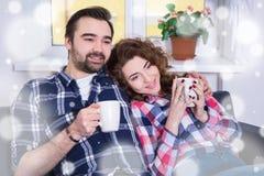 Concept d'hiver - jeune couple heureux se reposant sur le sofa avec des tasses de Image stock