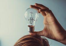 Concept d'idée d'ampoule Fille tenant l'ampoule sur la tête images libres de droits