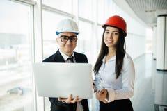 Concept d'ingénierie et d'architecture Ingénieurs travaillant à un chantier tenant un ordinateur portable, homme d'architecte tra photographie stock libre de droits