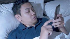 Concept d'intoxiqué de téléphone, homme asiatique avec le téléphone intelligent sur le lit photos stock