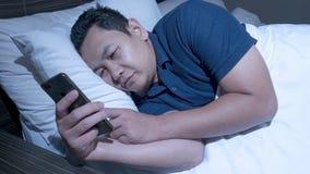 Concept d'intoxiqué de téléphone, homme asiatique avec le téléphone intelligent sur le lit photographie stock libre de droits