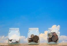 Concept d'investissement Pièces de monnaie croissantes en trois étapes dans le bott en verre clair Photo libre de droits