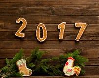 Concept d'an neuf Le schéma 2017 et coq de pain d'épice et chaussette pour des cadeaux, branche de sapin sur un fond en bois Photos stock