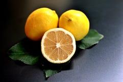 Concept d'un groupe de citrons, deux entiers et un demi- sur le fond noir photographie stock