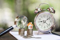 Concept d'une hypothèque, d'investissement immobilier, d'un modèle d'une maison et d'une loupe, de maison et de pièce de monnaie  images libres de droits