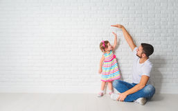 Concept. Dad measures growth of her child daughter at a wall Stock Photos