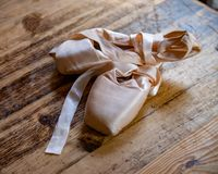 Pink ballet pointe shoes on a light brown black background. royalty free stock photos