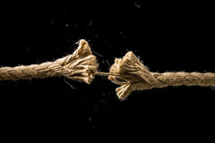 Concept of danger and risk. With two ends of a frayed worn rope held together by the last strand on the point of snapping, against a dark background with Stock Photos