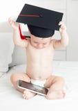 Concept de bébé futé Bébé mignon dans l'inte de lecture rapide de chapeau d'obtention du diplôme Photographie stock libre de droits