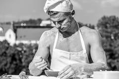 Concept de Baker Faites cuire ou chef avec les épaules musculaires et coffre couvert de la farine L'homme sur le visage occupé po photographie stock