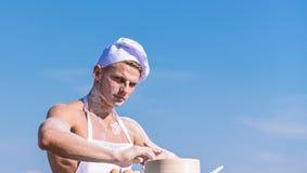 Concept de Baker L'homme sur le visage occup? porte faire cuire le chapeau et le tablier, ciel sur le fond Cuisinier ou chef avec photo libre de droits