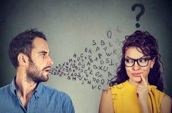 Concept de barrière linguistique Équipez parler à une jeune femme avec le point d'interrogation photos stock